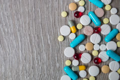 Lot of colorful medication and pills from above on grey wooden background. Copy space. Top view, frame. Painkillers, tablets, gene. A lot of colorful medication Stock Photos