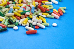 Lot of colorful pills on a blue background Stock Images