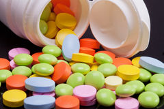 Lot of colorful pills with white box on black background Stock Images