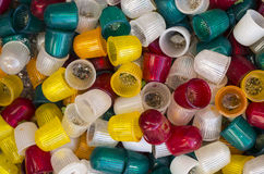 A lot of colorful plastic thimbles in the sand. Green , yellow red and white Royalty Free Stock Photography