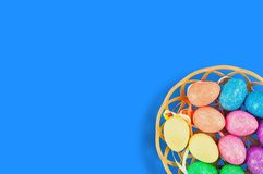 Lot of colorful and sparkling artificial eggs in brown wicker basket on blue table. Copy space for your text. View from above. Hap stock photo
