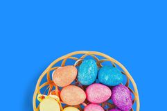 Lot of colorful and sparkling artificial eggs in brown wicker basket on blue table. Copy space for your text. View from above. Hap stock photos