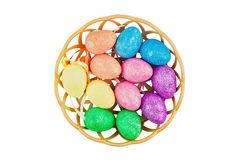 Lot of colorful and sparkling artificial eggs in brown wicker basket isolated on white background. Clipping path stock image
