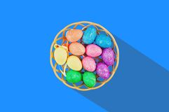 Lot of colorful and sparkling artificial eggs in brown wicker basket with long hard shadow in center of blue table. View from abov. E. Happy Easter celebration stock photography