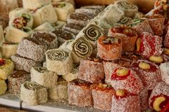 A bunch of oriental sweets rahat loachum on a table. A lot of couscous from oriental sweets rahat loachum on a table royalty free stock photo