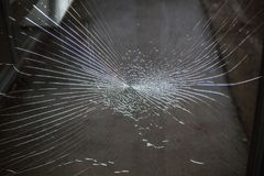 A lot of cracks on the glass. Cracks on glass on a dark background Stock Photography