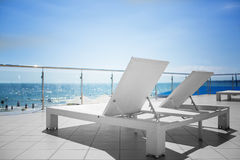 A lot of deck chairs at the transparent balcony of an expensive hotel. Beautiful sea landscape with plastic white chaise lounges. Stock Images
