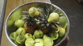 Lot of decor in silver bowls. Wood table with pine apples and pears and apples decor Stock Photo