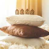 A lot of decorative cozy pillows and the inscription HOME stock image