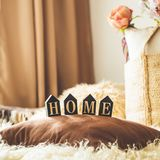 A lot of decorative cozy pillows and the inscription HOME stock images