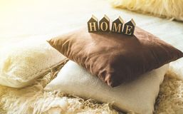 A lot of decorative cozy pillows and the inscription HOME royalty free stock photography