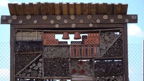 Big bug hotel for the useful and beneficial insects, 4k. A lot of different sections with wood and pots, with holes for the insects, in a big insect hotel stock video footage