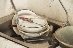 Lot of dirty dishes in the old kitchen. A lot of dirty dishes in the old poorly furnished kitchen stock photo