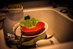 Lot of dirty dishes in the white sink in the kitchen. A lot of dirty dishes in the white sink in the kitchen messy domestic plate washing housework chores stock photo