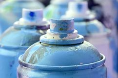 A lot of dirty and used aerosol cans of bright blue paint. Macro photograph with shallow depth of field. Selective focus on the. Spray nozzle royalty free stock photography