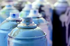 A lot of dirty and used aerosol cans of bright blue paint. Macro photograph with shallow depth of field. Selective focus on the. Spray nozzle royalty free stock photo