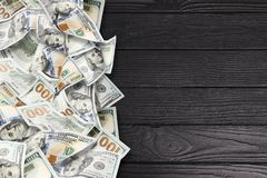 A lot of dollars on a black wooden background royalty free stock photos