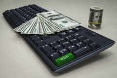 A lot of dollars on a computer keyboard. With the earn button Royalty Free Stock Photos