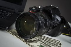 A lot of dollars near the camera and laptop stock photography