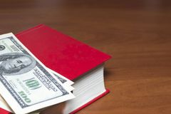 A lot of dollars on a red book. Mockup. Copy space. royalty free stock photo