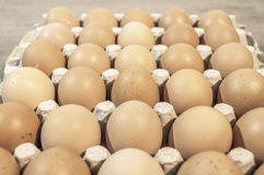 A lot of eggs in carton package on a wooden table for baking. A lot of eggs in carton package on a wooden table Royalty Free Stock Image
