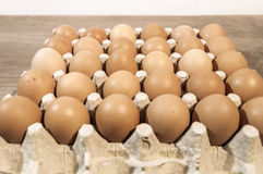 A lot of eggs in carton package on a wooden table ready for baki. A lot of eggs in carton package on a wooden table Stock Images