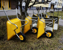 Lot of empty new yellow garden wheelbarrows in the yard Royalty Free Stock Photography