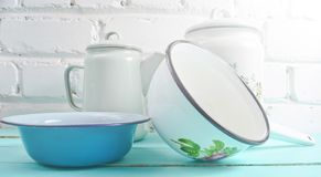 Lot of enameled dishes on a blue table against white brick wall background. Retro style cookware. Lot of enameled dishes on a blue table against white brick stock photo