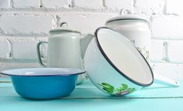 Lot of enameled dishes on a blue table against white brick wall background. Retro style cookware. Lot of enameled dishes on a blue table against white brick stock photos