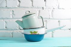 Lot of enameled dishes on a blue table against white brick wall background. Retro style cookware. Lot of enameled dishes on a blue table against white brick stock photography
