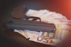 Lot of euro banknotes. Lot of euro banknotes and gun on the table Royalty Free Stock Photography