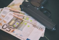 Lot of euro banknotes. Lot of euro banknotes and gun on the table Stock Photography