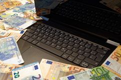 A lot of euro banknotes lying around notebook. With German keyboard layout stock photos
