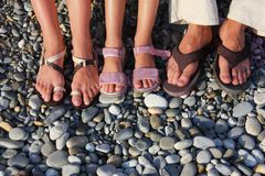 Lot of feet on the stones. Family with girl Stock Photo