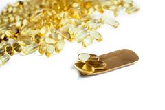 A lot of fish oil omega 3 6 9 capsules on a brass golden spoon. sports nutrition healthy food nutritional supplements healthy stock photography