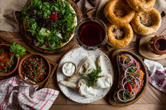 A lot of food on the wooden table. Georgian cuisine. Top view. Flat lay . Khinkali and Georgian dishes.  Stock Photos