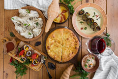 A lot of food on the wooden table. Georgian cuisine. Top view. Flat lay . Khinkali and Georgian dishes.  Stock Image