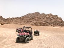 A lot of four-wheeled multicolored powerful fast off-road four-wheel drive buggies, cars, SUVs in the sandy hot desert on the sand. In the parking lot against Stock Image