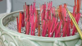Fragrant red sticks for good luck near the traditional small Buddhist altar in the garden. Lot of fragrant red sticks for good luck near the traditional small stock footage