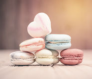 A lot of french colorful macarons on a woody floor in vintage to Stock Photo