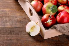 fresh ripe apples in a wooden tray and half an apple on a brown wooden background stock photo
