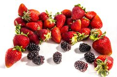 A lot of fresh sweet red good strawberry`s with some blackberry`s. The garden strawberry or simply strawberry; Fragaria × ananassa is a widely grown hybrid Royalty Free Stock Image