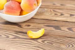 Lot of fresh whole ripe peaches in white ceramic bowl and one slice of peach separately. On rustic old wooden planks royalty free stock photos