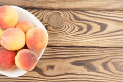 Lot of fresh whole ripe peaches in white ceramic bowl. On rustic old wooden planks royalty free stock photos
