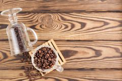 Lot of fried coffee beans in transparent glass for mulled wine on pallet near coffee beans poured out of glass stock photography