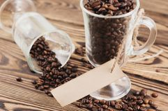 Lot of fried coffee beans in transparent glass for mulled wine with rectangle blank paper on rope royalty free stock image