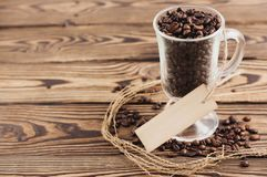 Lot of fried coffee beans in transparent glass for mulled wine with rectangle blank paper on rope near scattered coffee beans stock photography