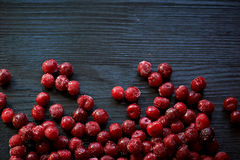 A lot of frozen cherry without sticks on a wooden black background. Vitamins and a healthy diet Stock Images