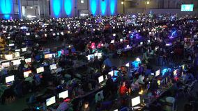 A lot of gamers playing on computer games in the great hall.