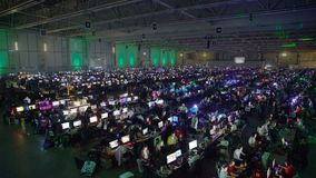 A lot of gamers playing on computer games in the great hall. HELSINKI, FINLAND - JULY 05, 2017: A lot of gamers playing on computer games in the great hall. The stock footage
